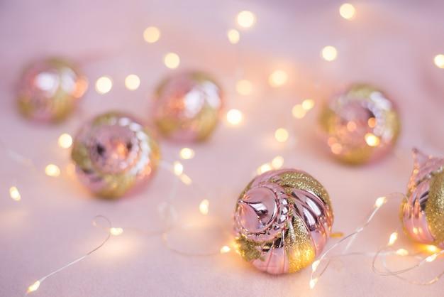 Weihnachtsspielwaren auf einer hellrosa oberfläche mit lichtern
