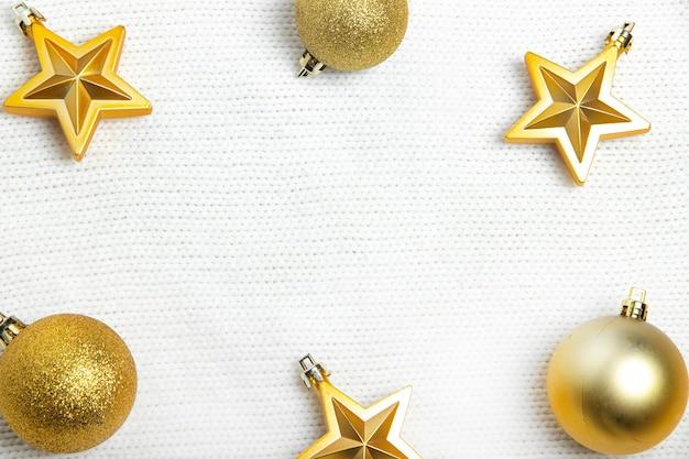 Weihnachtsspielzeug auf einem pulloverlayout. neujahr und weihnachten. urlaubslayout. speicherplatz kopieren. neues jahr 2021. artikel über das neue jahr. goldene kugeln.