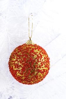 Weihnachtsspielzeug auf schneeweißer weihnachtsbaumnahaufnahme lokalisiert auf weiß