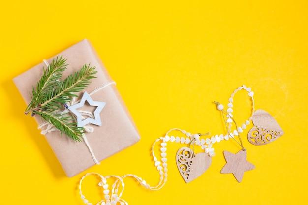 Weihnachtsspielzeug aus holz, band und geschenkbox in kraftpapier verpackt und mit einem holzstern und einem fichtenzweig auf gelbem hintergrund verziert, öko-weihnachtskonzept