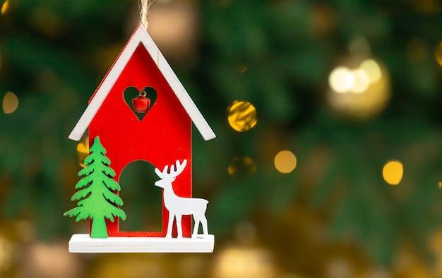 Weihnachtsspielzeug aus holz. haus mit hirsch.