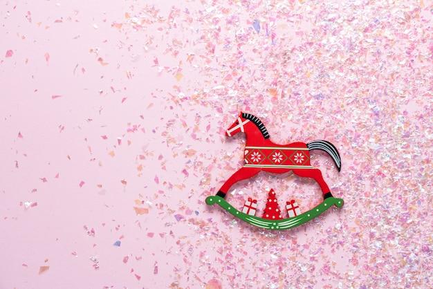 Weihnachtsspielzeug des schaukelpferds auf rosa mit funkeln. flach liegen