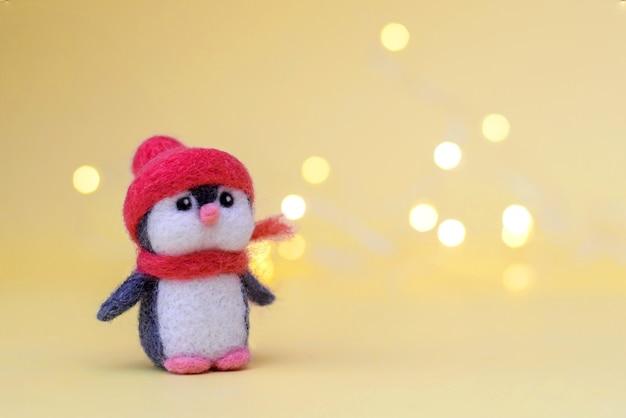 Weihnachtsspielzeug gefilzte wolle niedlichen kleinen pinguin in einem winter roten hut und schal auf einem gelben hintergrund mit bokeh, kopienraum