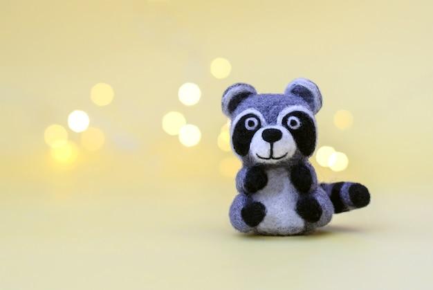 Weihnachtsspielzeug gefilzte wolle niedlichen kleinen waschbären auf einem gelben hintergrund mit bokeh, kopienraum