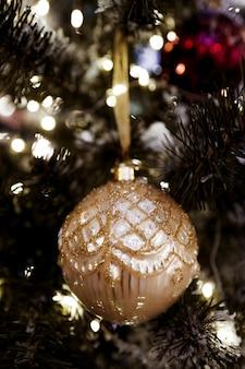 Weihnachtsspielzeug goldglänzender ball, der am weihnachtsbaum hängt