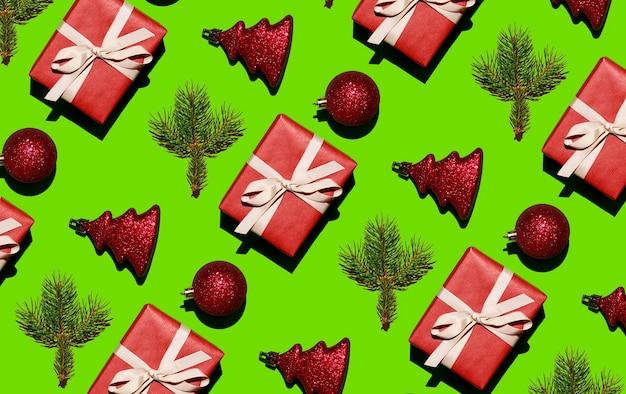 Weihnachtsspielzeug kugeln weihnachtsbaum zweig und ein festliches geschenk auf grünem hintergrund weihnachtsnaht...