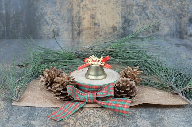 Weihnachtsspielzeug mit bogen und zwei tannenzapfen auf marmorhintergrund. hochwertiges foto