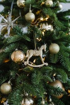 Weihnachtsspielzeug pferd und bälle hängen am baum, geschmückt mit lichtern