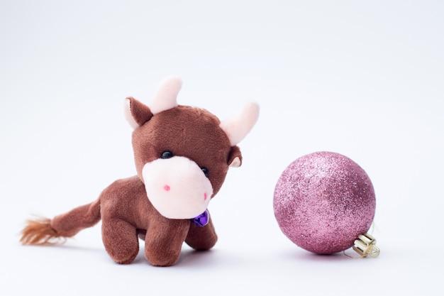 Weihnachtsspielzeug stiersymbol des neuen jahres 2021 mit weihnachtskugel.