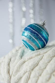 Weihnachtsspielzeug und gestreifter ball mit glitzern auf gestricktem wollpullover