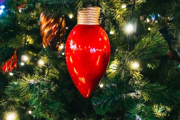 Weihnachtsspielzeug und girlande am weihnachtsbaum. nahaufnahme
