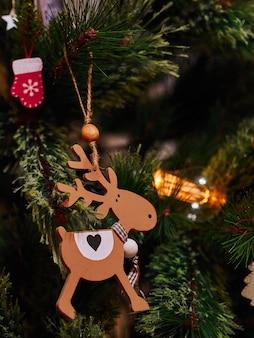 Weihnachtsspielzeug und taschenlampen aus holzhirschen auf dem weihnachtsbaum
