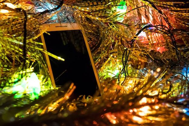 Weihnachtsspielzeug und weißes smartphone in leuchtenden weihnachtslichtern. leerer bildschirm für foto oder text. platz kopieren