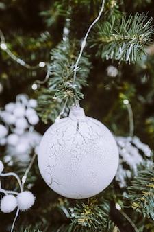 Weihnachtsspielzeug weißer silberner glänzender ball, der am weihnachtsbaum hängt