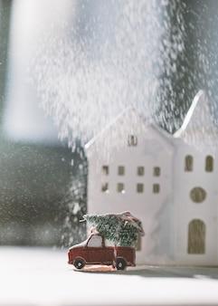 Weihnachtsspielzeugauto auf dem hintergrund des hauses
