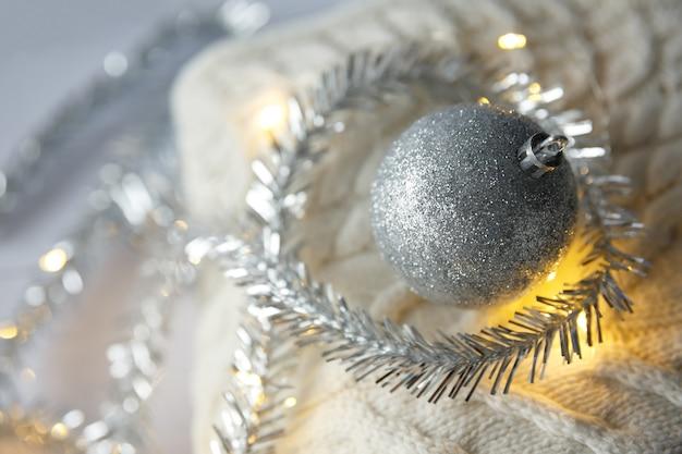 Weihnachtsspielzeugball mit funkelnden girlanden auf gestricktem wollpullover