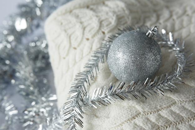 Weihnachtsspielzeugball mit glitzern auf gestricktem wollpullover