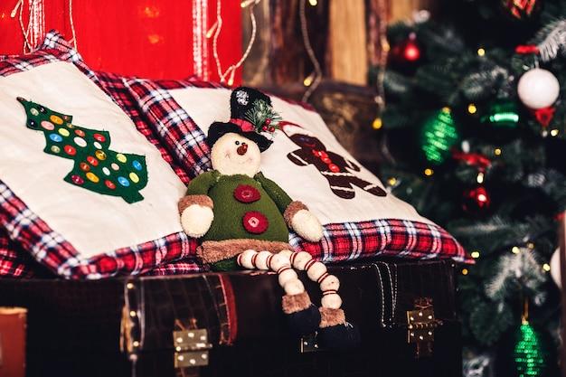Weihnachtsspielzeugelfe sitzt auf koffer auf oberfläche des weihnachtsbaumes.