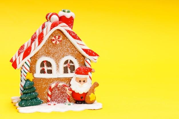 Weihnachtsspielzeughaus mit weihnachtsmann auf gelbem hintergrund