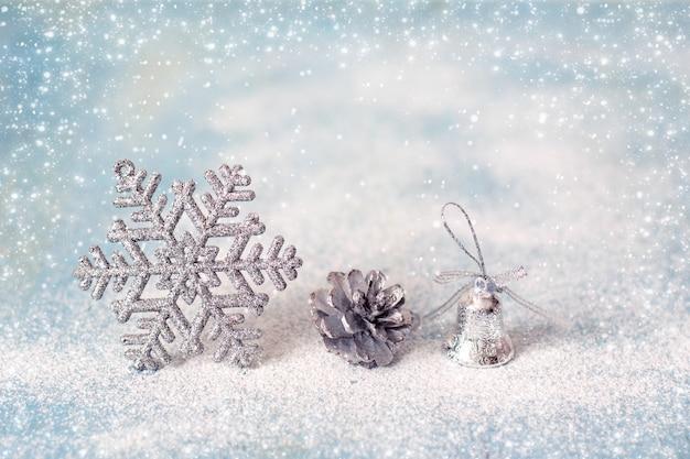 Weihnachtsspielzeugschneeflocke, tannenzapfen, glocke auf winterurlaubshintergrund