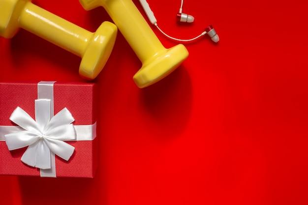 Weihnachtssportkomposition mit hanteln, kleinen ohrhörern, roter geschenkbox