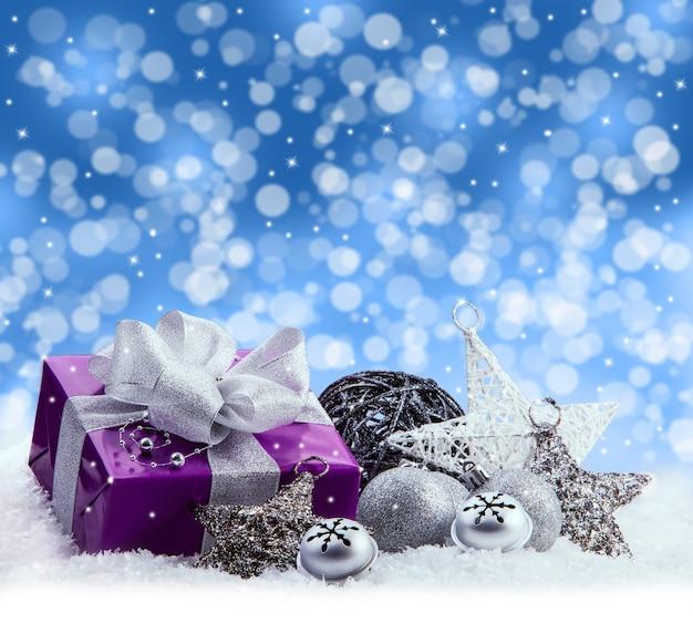 Weihnachtsstillleben dekoration. lila geschenk mit holzkugel und traditionellen sternen und jingle bells auf schnee gelegt. kalter blauer hintergrund mit illustrierten schneeflocken.