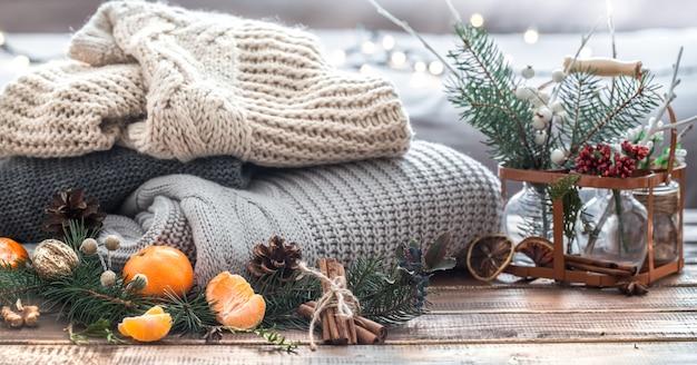 Weihnachtsstillleben eines lebenden weihnachtsbaumes, dekorationen und festlicher kranz auf einem hintergrund von gestrickten kleidern