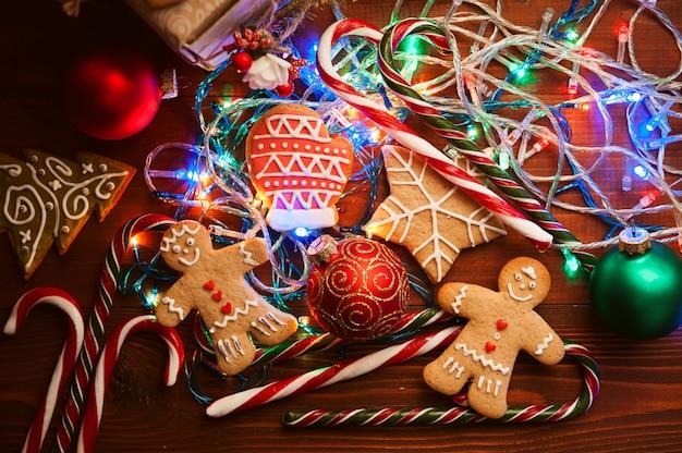 Weihnachtsstillleben. hausgemachte ingwerkekse, rohrzucker, auf einer holzoberfläche.