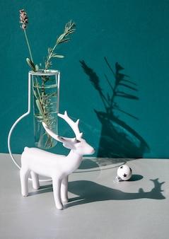 Weihnachtsstillleben, minimale anordnung mit winterblumen in moderner glasvase und weißem weihnachtsdekor