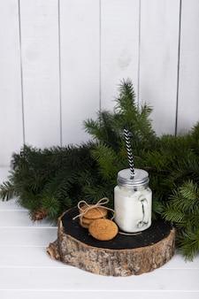 Weihnachtsstillleben-szene. duftkerze in einem glas und kekse auf einem dicken holzklotz in der nähe eines fichtenzweigs
