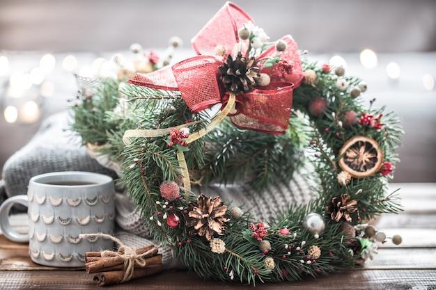 Weihnachtsstillleben von bäumen und dekorationen, festlicher kranz vor dem hintergrund von strickwaren und schönen tassen