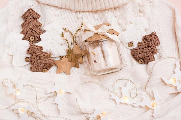 Weihnachtsstimmung. glas mit paste, gestrickten tannen, holzspielzeug und einer hirschgirlande auf einem weißen pullover. handwerksdekor. kein verlust. draufsicht