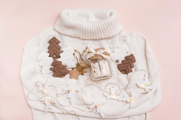 Weihnachtsstimmung. glas mit paste, gestrickten tannen, holzspielzeug und einer hirschgirlande auf einem weißen pullover. handwerksdekor. kein verlust