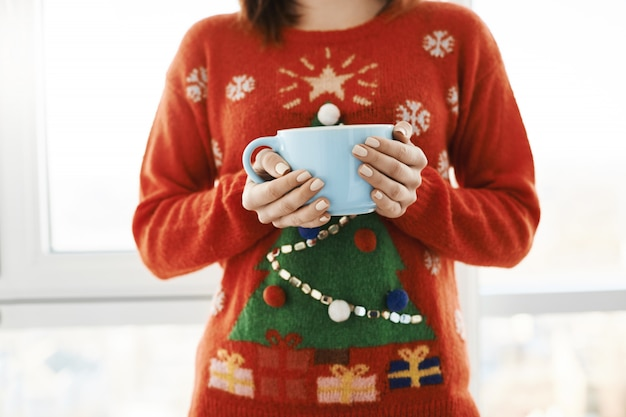Weihnachtsstimmung ist in der luft. kurzer schuss der frau zu hause, die einen lustigen weihnachtspullover mit baum trägt, eine riesige tasse mit kaffee hält und über dem fenster steht und sich wohl und gemütlich fühlt