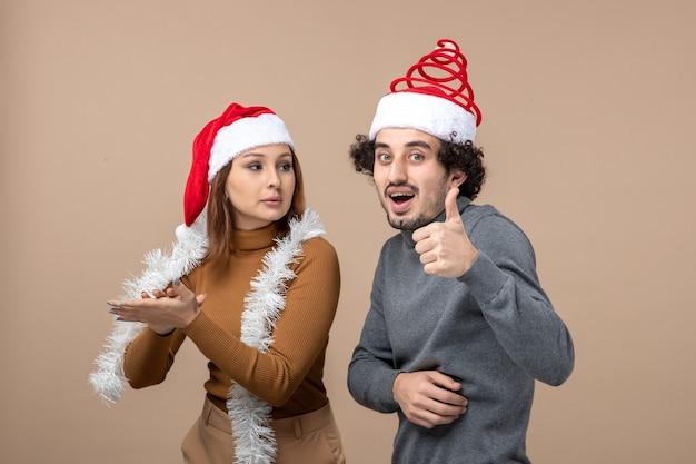 Weihnachtsstimmung mit aufgeregten coolen zufriedenen reizenden reizenden paaren, die rote weihnachtsmannhüte tragen, die zusammen genießen