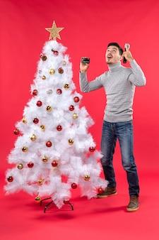 Weihnachtsstimmung mit dem jungen mann, der nahe geschmücktem weihnachtsbaum steht und oben mikrofon und telefon hält