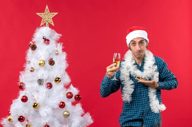 Weihnachtsstimmung mit dem selbstbewussten jungen mann mit weihnachtsmannhut in einem blau gestreiften hemd, das ein glas wein nahe weihnachtsbaum erhebt