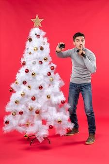 Weihnachtsstimmung mit dem stolzen kerl, der nahe geschmücktem weihnachtsbaum steht und mikrofon und telefon hält, die stille geste machen