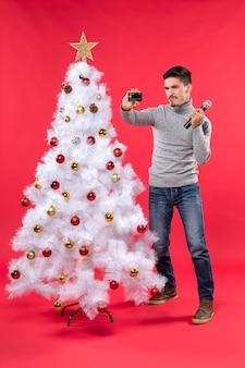 Weihnachtsstimmung mit dem stolzen kerl, der nahe geschmücktem weihnachtsbaum steht und mikrofon und telefon hält