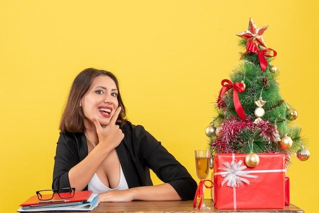 Weihnachtsstimmung mit der jungen glücklichen geschäftsdame, die im büro auf lokalem gelbem hintergrund sitzt