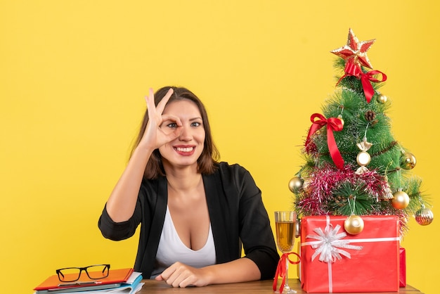 Weihnachtsstimmung mit der jungen glücklichen geschäftsdame, die spektakuläre geste auf gelb macht