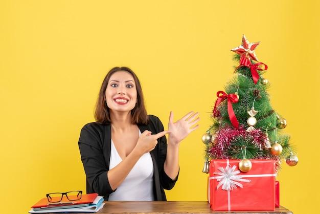 Weihnachtsstimmung mit der jungen schönen frau, die ihre hand auf büro zeigt