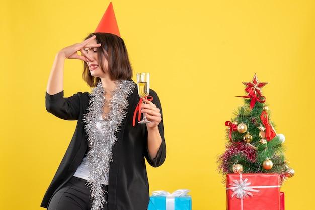 Weihnachtsstimmung mit der schönen dame des sauren gesichts, die wein im büro auf gelb hält