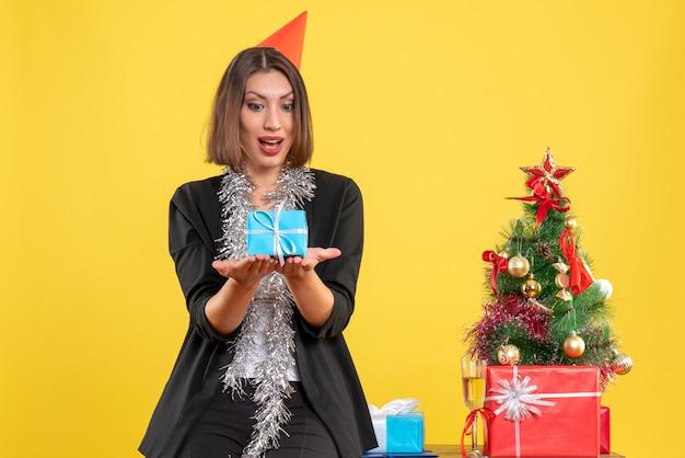 Weihnachtsstimmung mit der schönen dame, die geschenk glücklich im büro auf gelb hält
