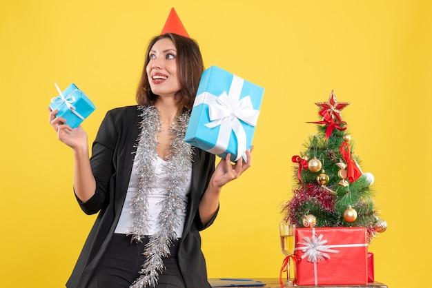 Weihnachtsstimmung mit der schönen dame, die geschenke glücklich im büro auf gelb hält
