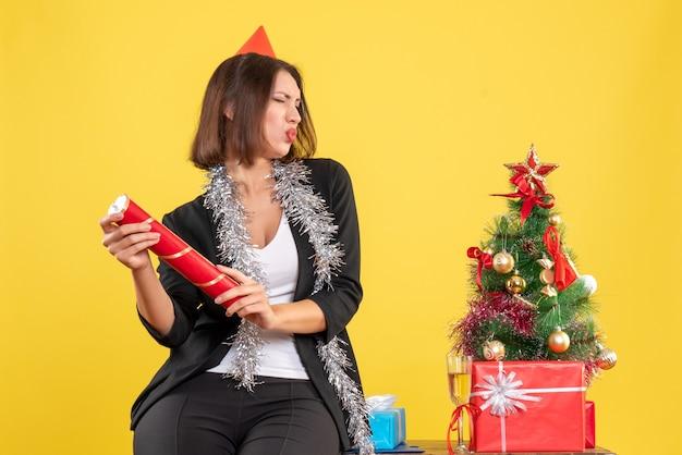 Weihnachtsstimmung mit der schönen dame, die im büro auf gelb stolz ist