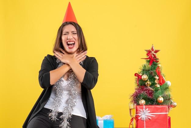 Weihnachtsstimmung mit der schönen dame, die sich im büro auf gelb emotional fühlt