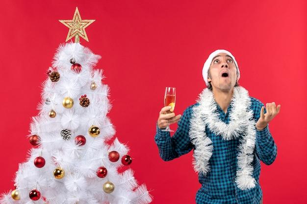 Weihnachtsstimmung mit emotionalem jungem mann mit weihnachtsmannhut in einem blauen gestreiften hemd, das ein glas wein hält, das nahe weihnachtsbaum schaut