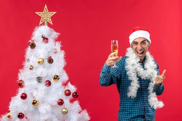 Weihnachtsstimmung mit emotionalem verrückten jungen mann mit weihnachtsmannhut in einem blauen gestreiften hemd, das ein glas wein nahe weihnachtsbaum hält