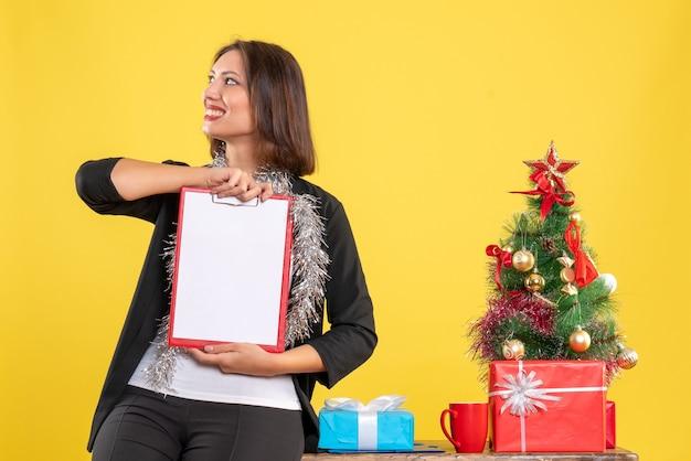 Weihnachtsstimmung mit emotionaler schöner dame, die im büro steht und dokumente hält, die etwas im büro auf gelb betrachten